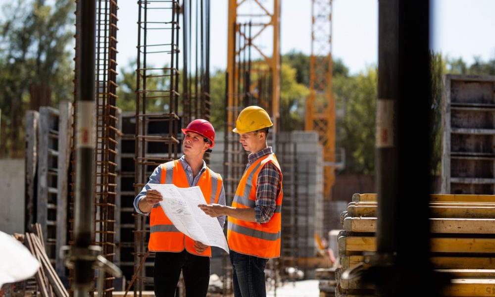 Construction manager and engineer dressed in orange work vests and hard helmets explore construction documentation on the building site near the steel frames . .